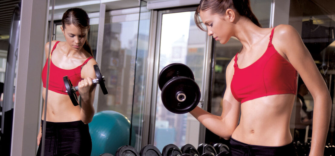 Young woman using Dumbbells in Health Club