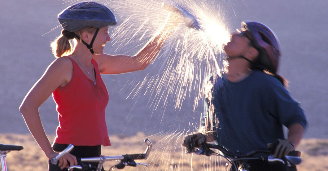 Woman pouring water on Man after Bike Ride